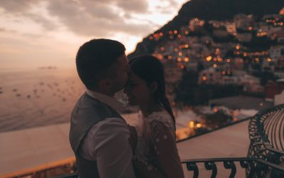 Photo of a married couple standing on the terrace and enjoying in their love and amazing view of Positano, Italy