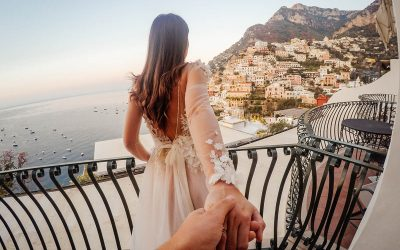 Photo of a beautiful bride holding hands with her groom on a terrace with a view of Positano, Italy
