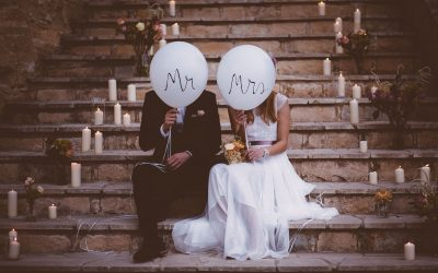 Bride and groom sitting together on rustic staircase and holding balloons
