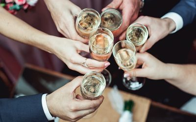 People hold in hands glasses with white wine. wedding party. friends toasting with a champagne above white table